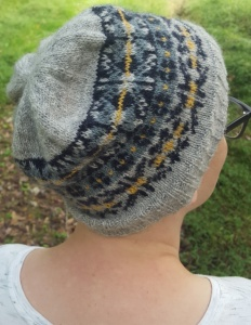 Back of a woman's head modeling the Rionnag Hat, a Fair Isle knitted beanie.