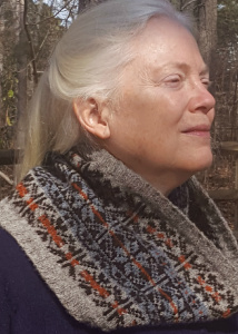 Close up of a woman modeling the Rionnag Cowl, a Fair Isle knitted cowl.