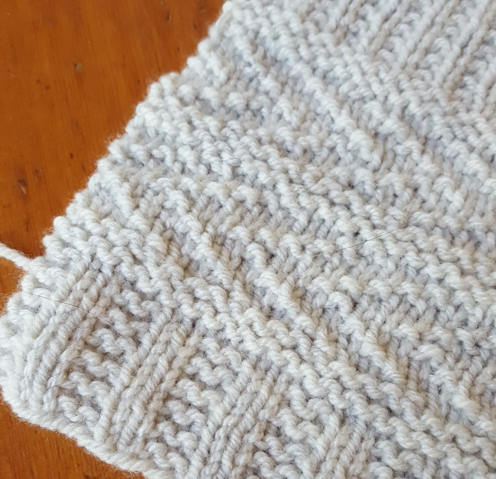 Photo shows a knitted swatch with a textured pattern in light gray yarn.