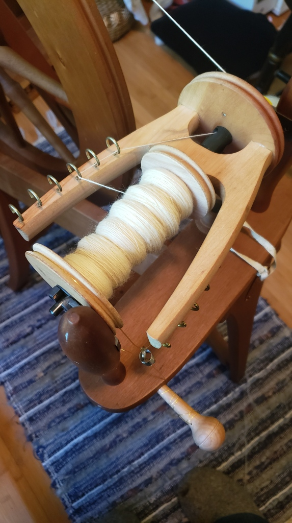 A spinning wheel flyer with a bobbin of Cormo yarn.