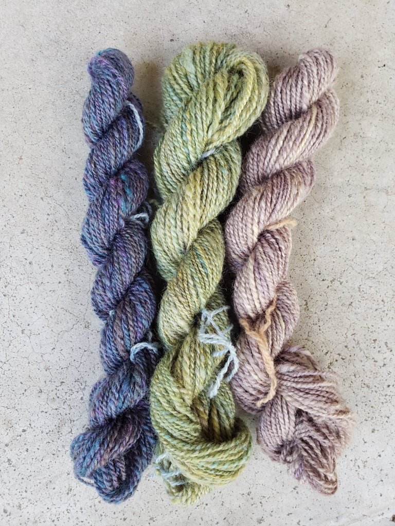 Three mini skeins of handspun yarn in blue, yellow and lavender.