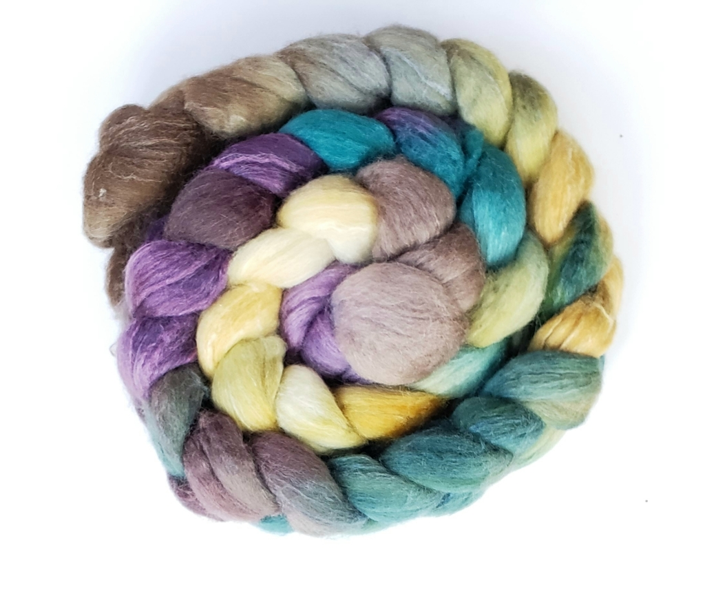 A braid of handyed fiber in shades of teal, purple, yellow and brown.