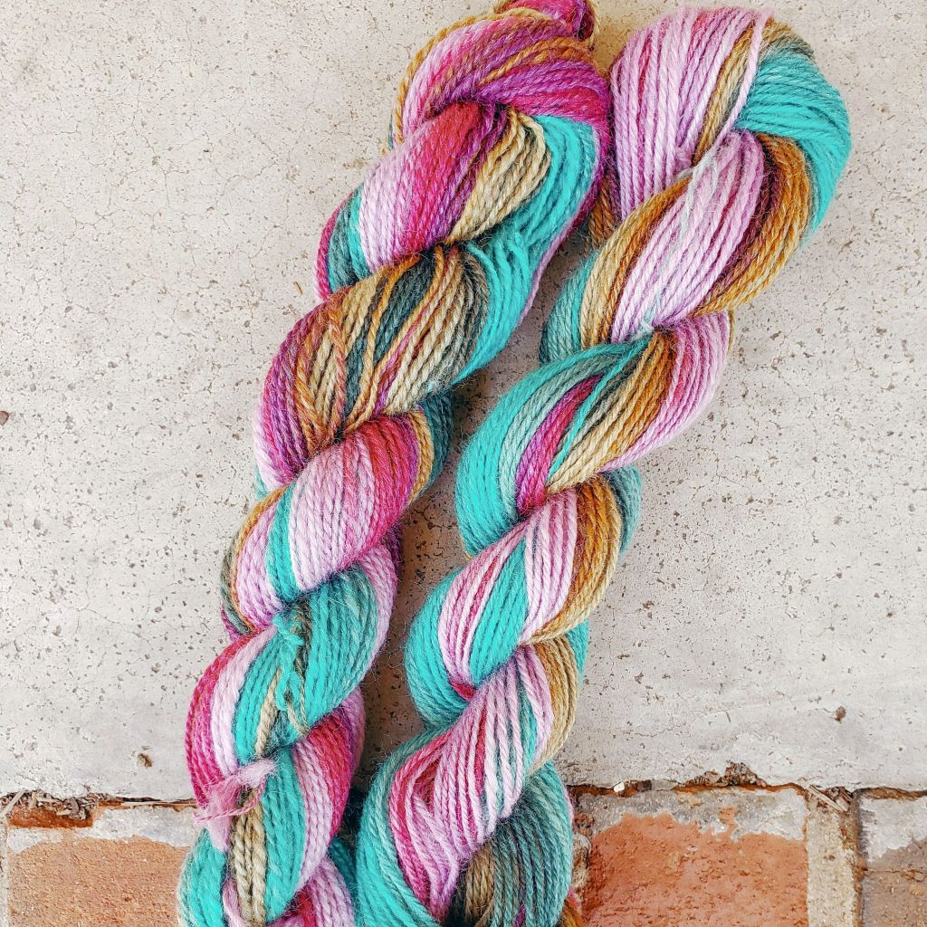 Two small skeins of handspun yarn in shades of pink, turquoise and gold on a concrete and brick step.