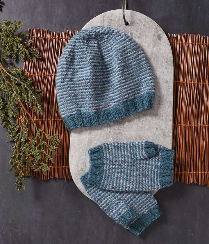 A teal and gray striped hat and mitts on a stone board lay on a bamboo mat. An evergreen bough sits to the left.