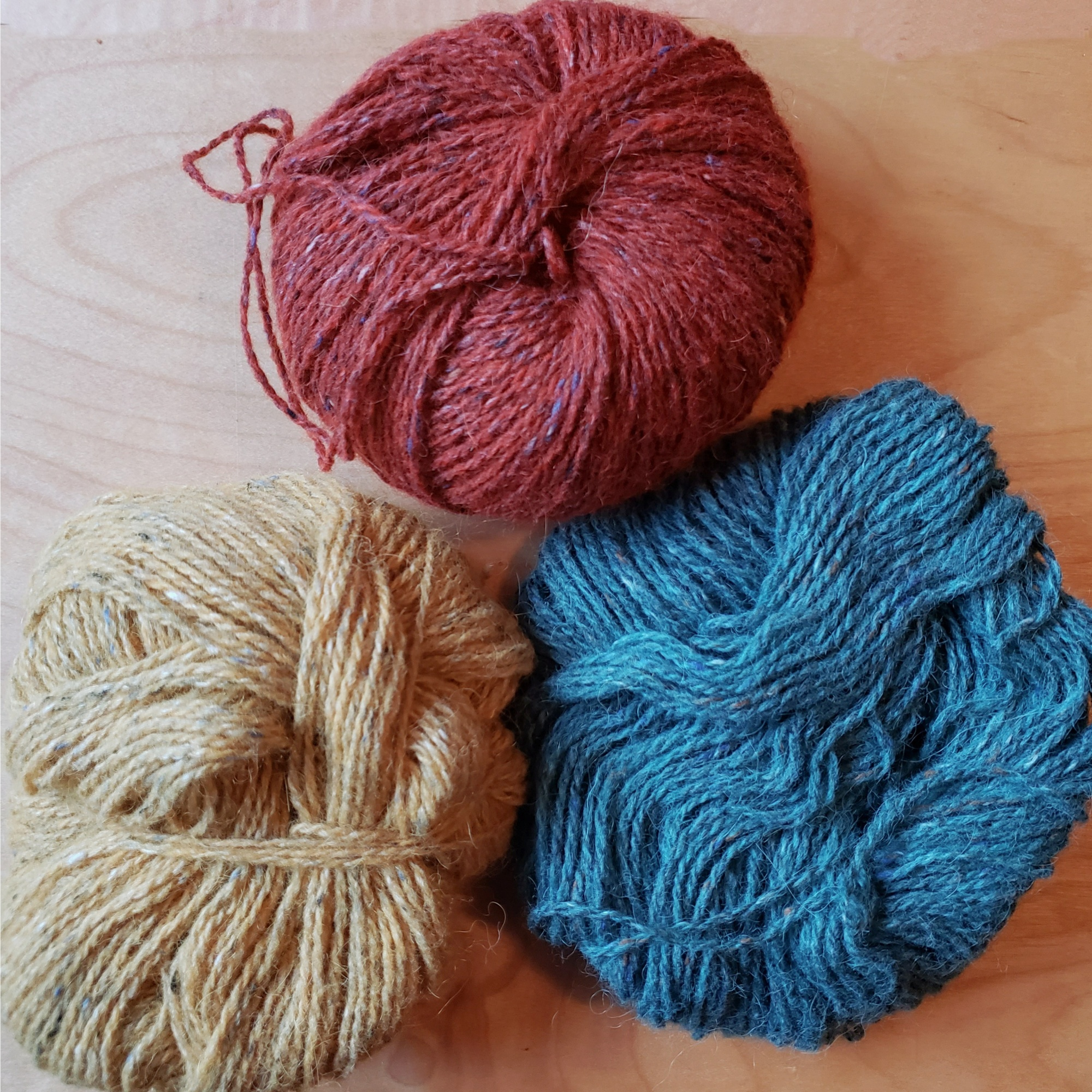 A trio of yarn balls in rust, teal, and gold