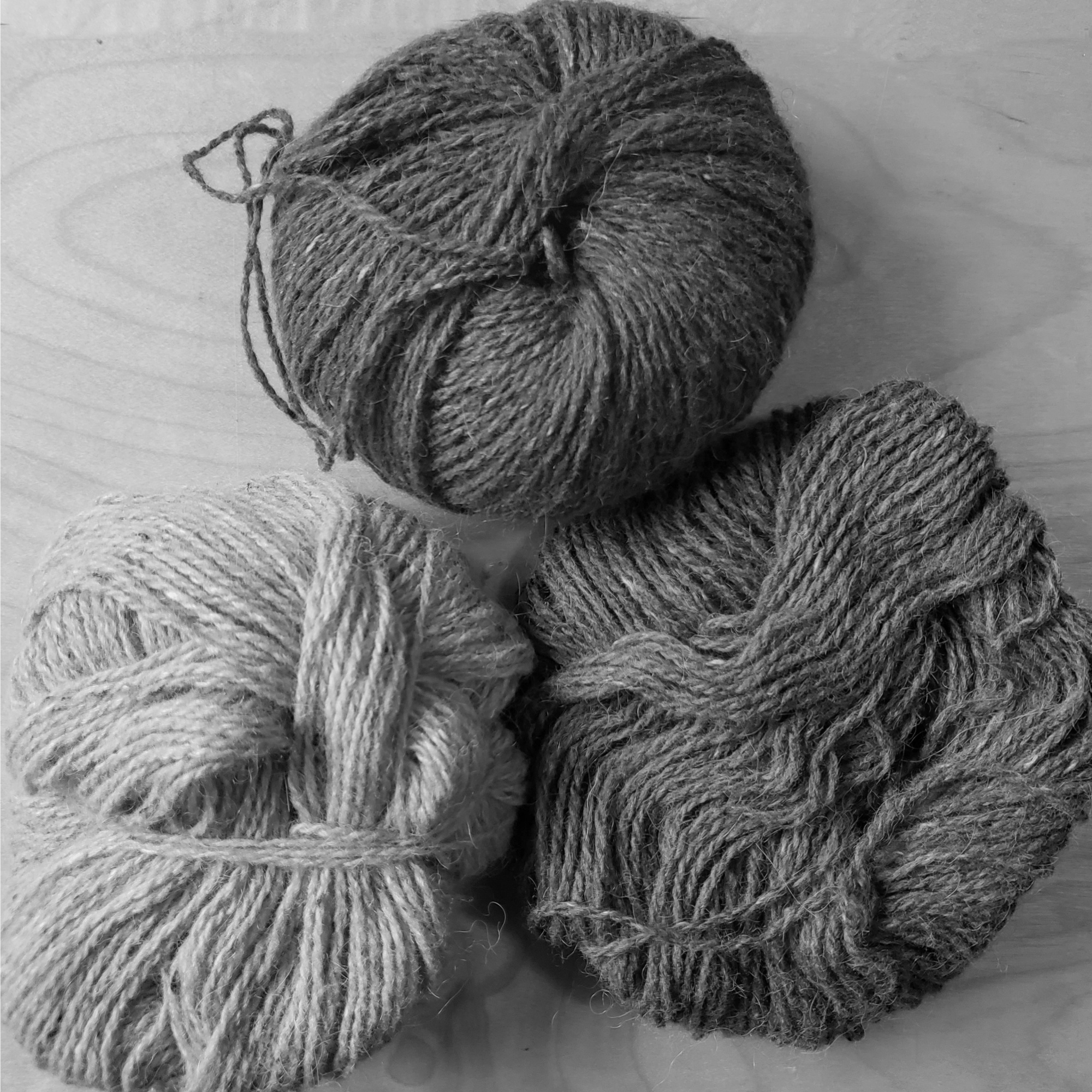 a trio of yarn balls in gray scale showing their contrast