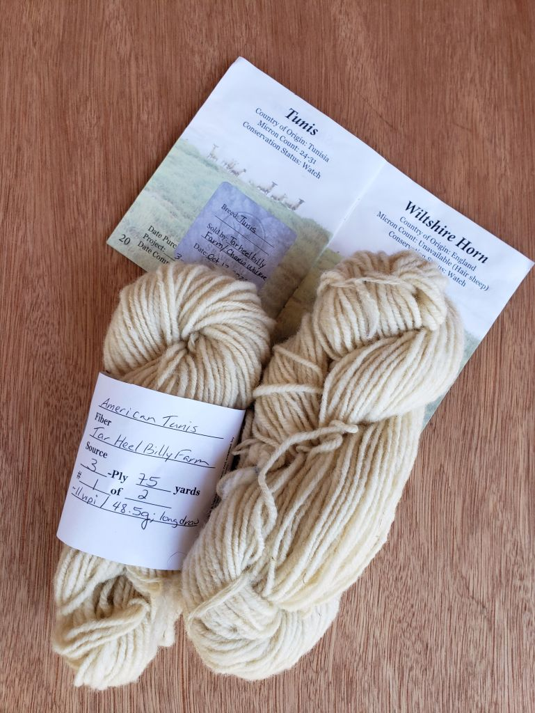 Two skeins of woolen-spun Tunis lambswool next to a SE2SE passport