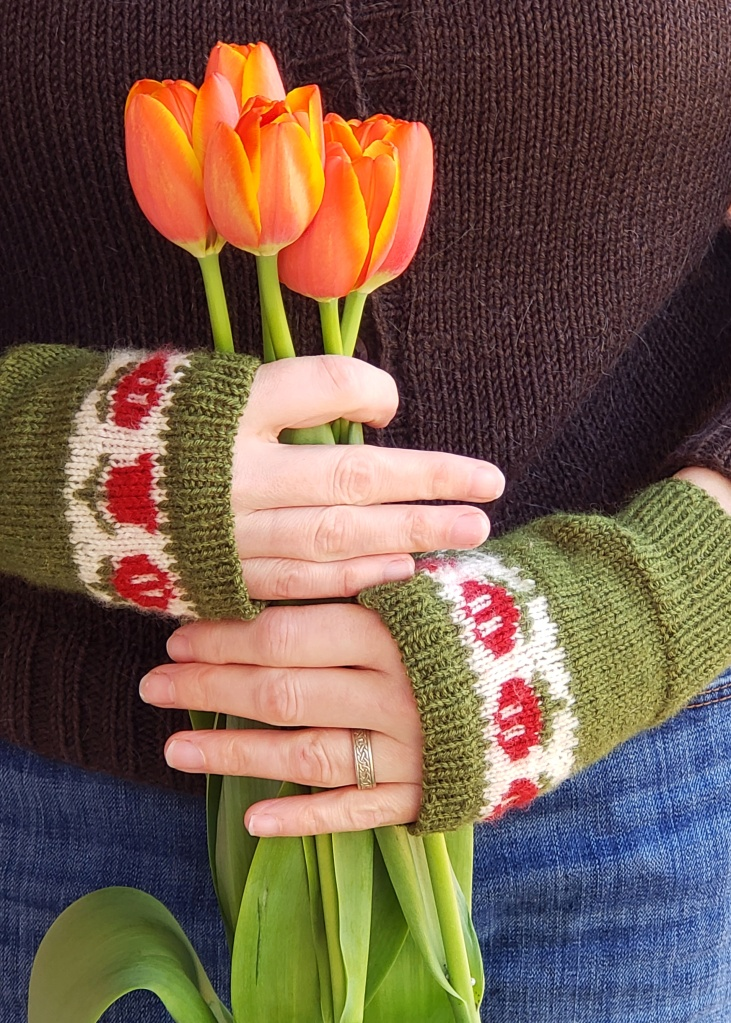 Kerry wears handknit Fair Isle fingerless mitts in green with red tulips on a white backround. She is holding orange tulips.