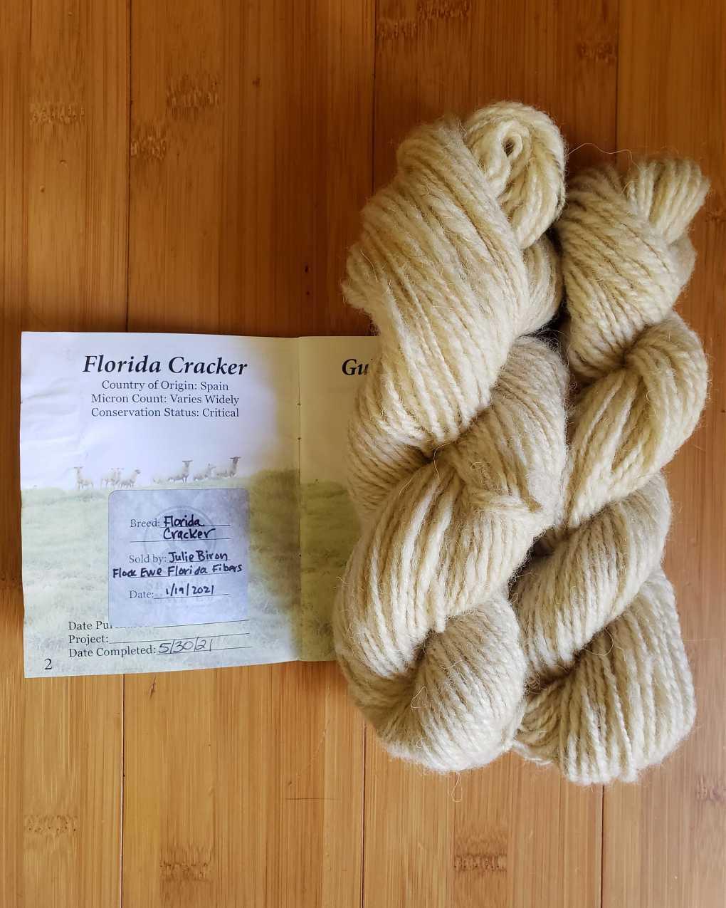 Two skeins of handspun Florida Cracker yarn next to a stamped SE2SE passport page.