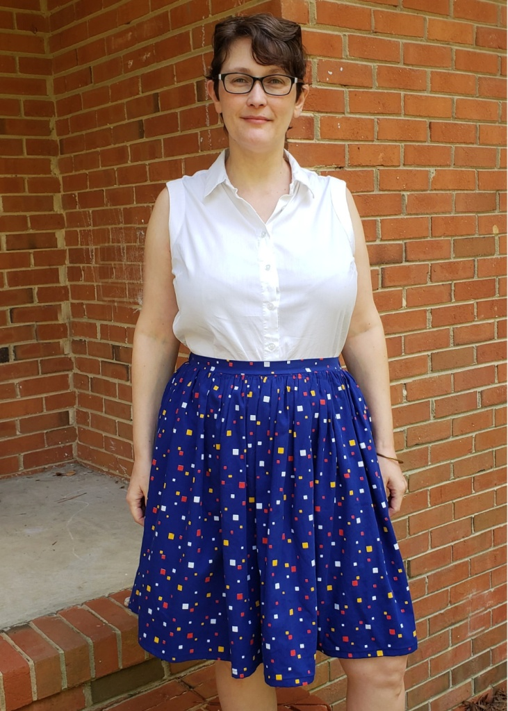 A middle-aged woman wears a white sleeveless shirt and a royal blue full skirt with geometric print.