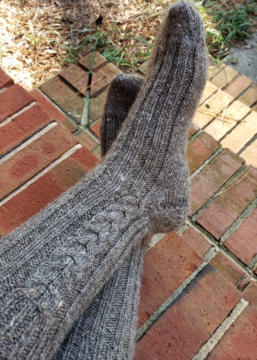 The author's feet, crossed and wearing gray wool cabled socks, rest on a brick staircase.