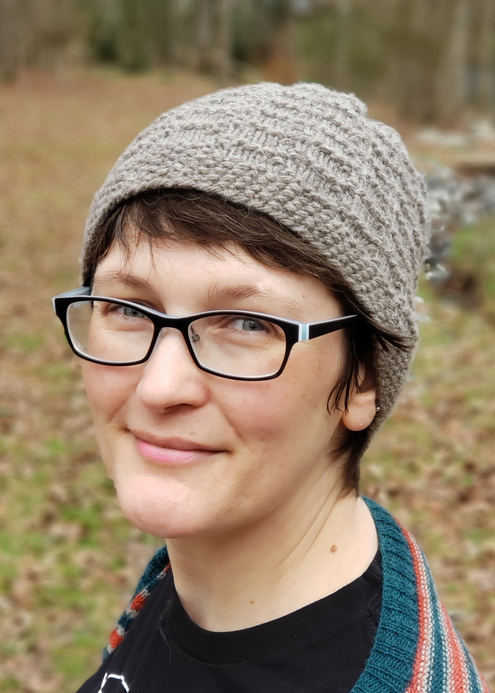 Photo of the designer looking sideways into the camera and wearing a handknit hat and sweater.